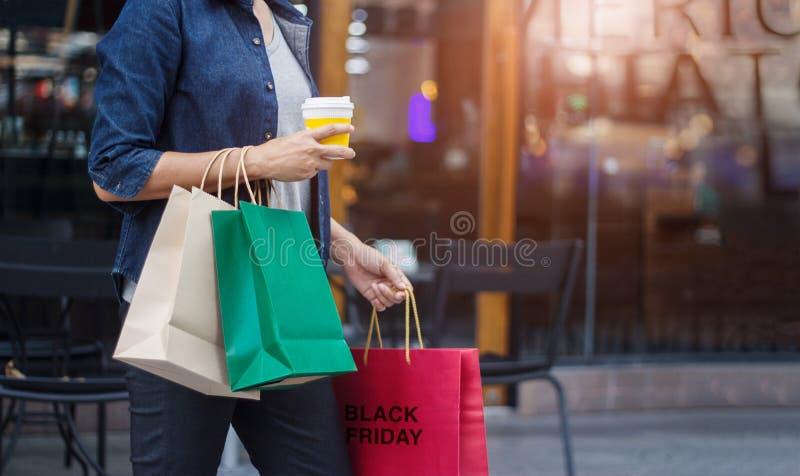 Vendredi noir Femmes avec la tasse de café tenant des sacs à provisions photos stock