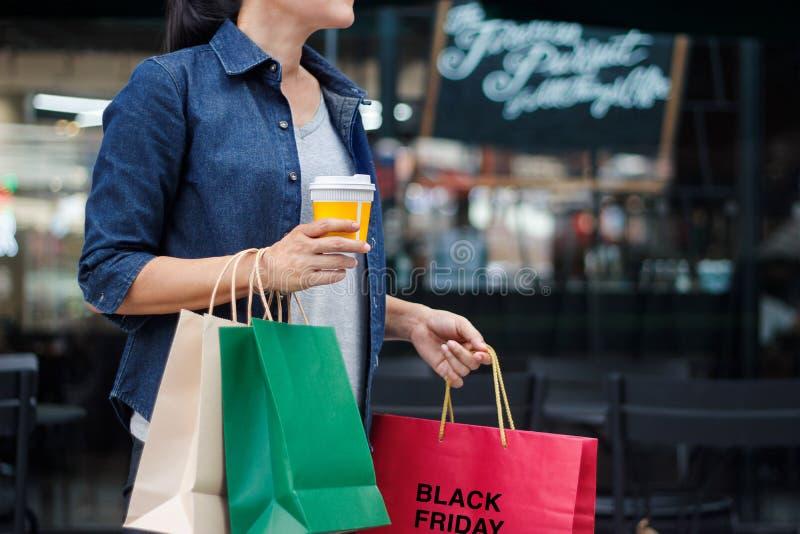 Vendredi noir Femmes avec la tasse de café, tenant des sacs à provisions images stock