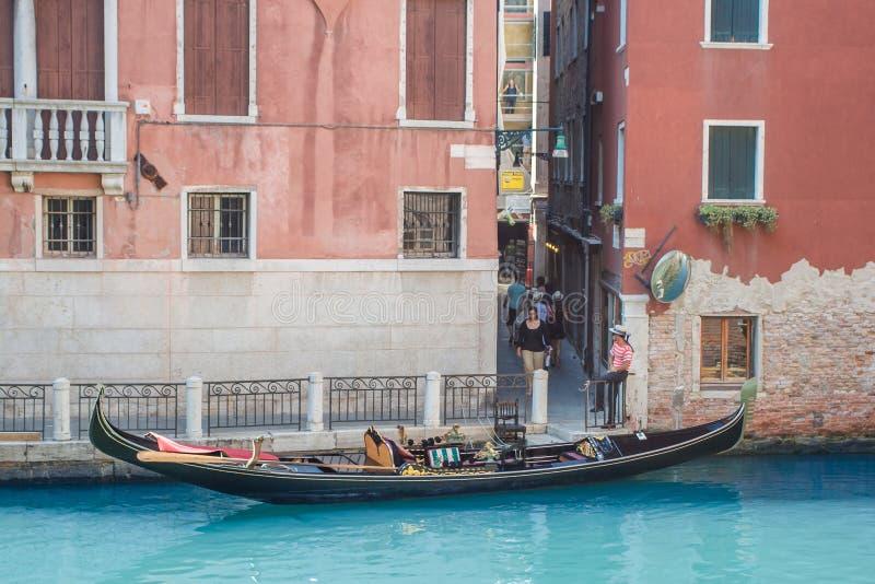 Venecia como es - ciudad en el agua, góndola parqueó en canal y gondolero en camisa tradicional y pintó la cara que esperaba foto de archivo