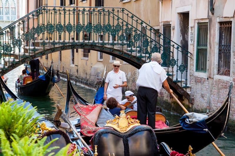 Venecia, Italia - 16 de agosto de 2013: el cantante canta a la mujer en la góndola en el canal en el fondo foto de archivo libre de regalías