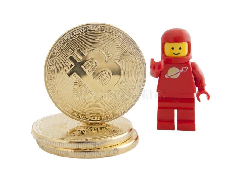 Venecia, Italia - 7 de enero de 2018: Un astronauta como figura de Lego que se coloca al lado de Bitcoin acuña, el 7 de enero de  imagen de archivo libre de regalías