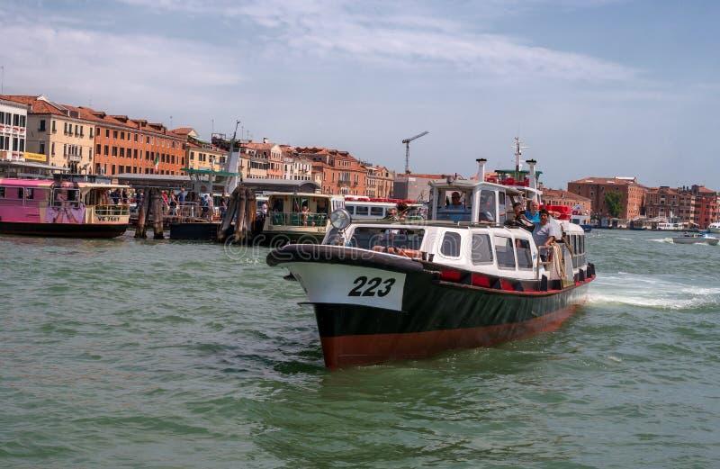Venecia, Italia - 7 de mayo de 2018: El autobús del agua de Vaporetto con los turistas flota a lo largo de la 'promenade' En el m fotografía de archivo libre de regalías