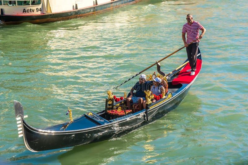 Venecia, Italia - 15 08 2018: Góndolas tradicionales en el canal estrecho foto de archivo
