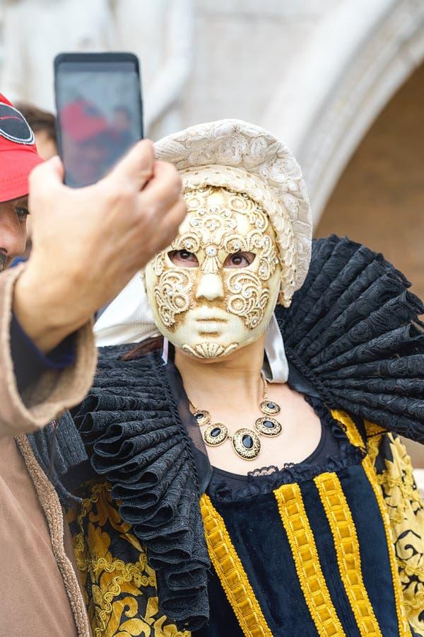 Venecia, Italia - 23 02 2019: La máscara y el hombre hermosos toman una foto en el teléfono móvil en la Plaza de San Marcos duran fotos de archivo
