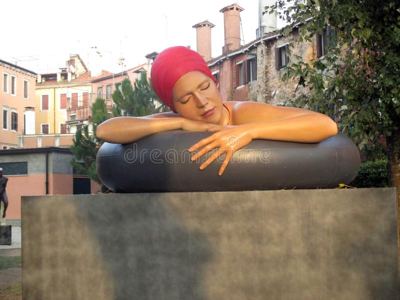 Venedig Biennale 2017 storartade kvinnliga skulptur - härlig kvinna med baddräkten som sover Giardini Italien arkivbild