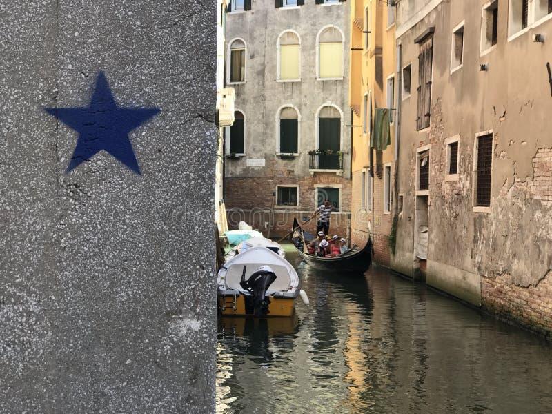 Venedig, den storslagna kanalen och två turister royaltyfria foton