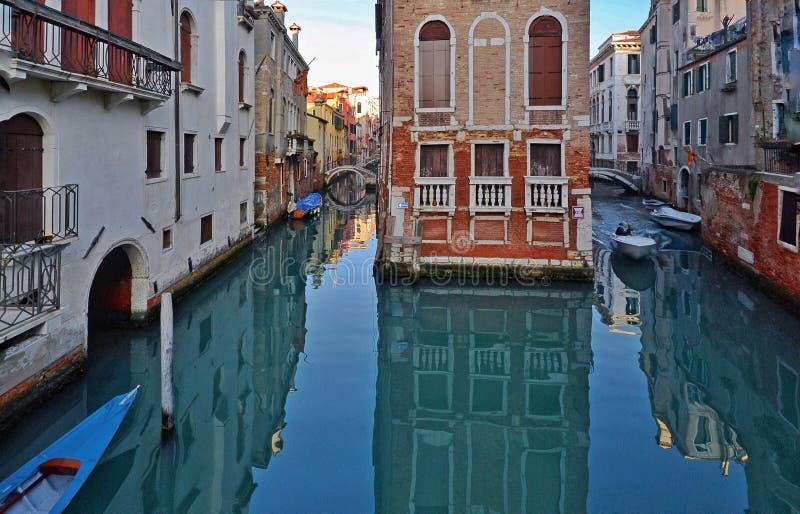 Venedig forntida slott i mitt av kanalen Ett litet fartyg seglar arkivbild