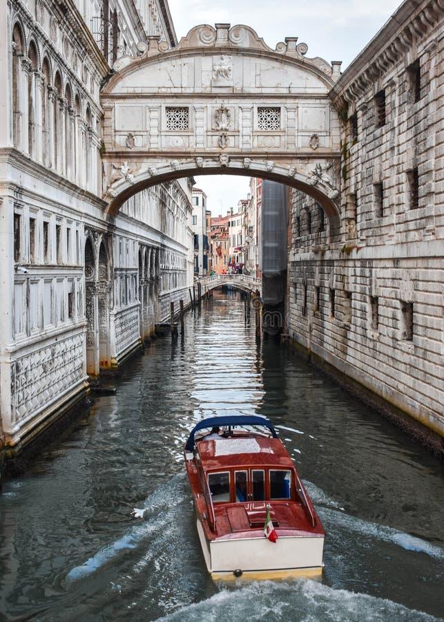 Venedig gata med den härliga bron och det röda fartyget royaltyfri bild