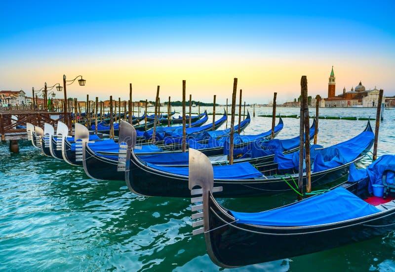Venedig, gondoler eller gondole på solnedgång och kyrka på bakgrund fotografering för bildbyråer