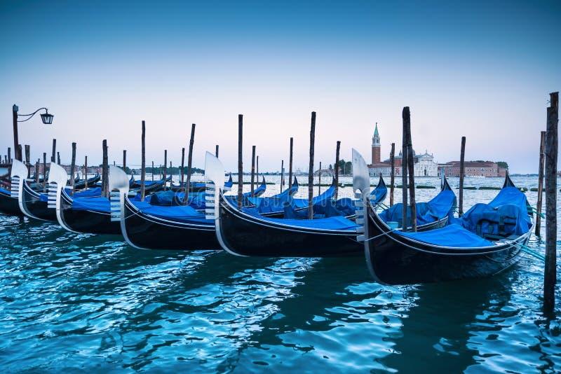 Venedig, gondoler eller gondole på solnedgång och kyrka på bakgrund arkivbilder