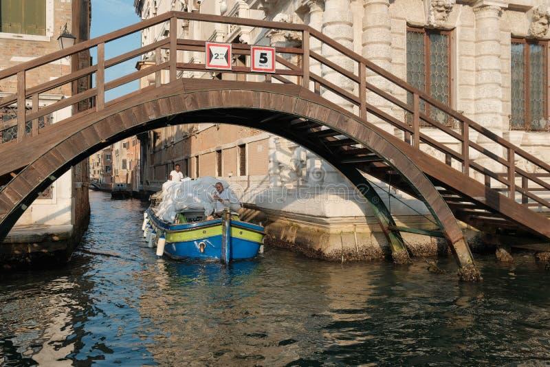Venedig Italien, en laden pråm seglar längs en kanal under en bro royaltyfri foto
