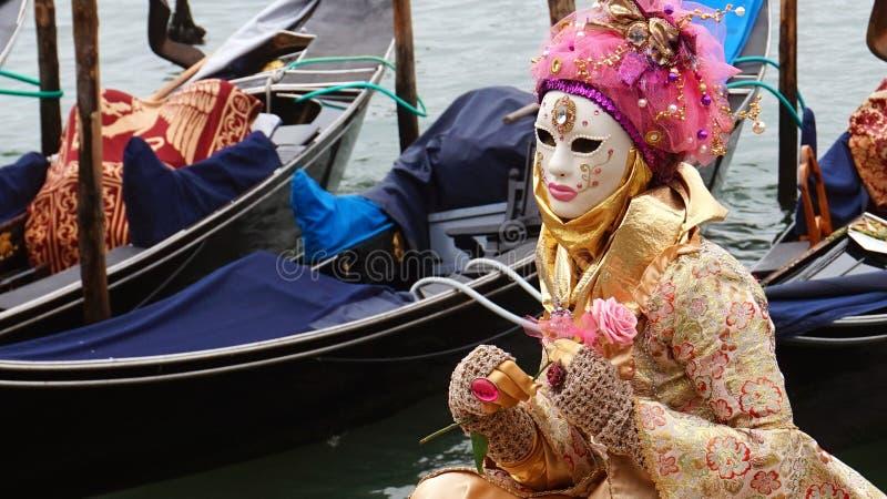 VENEDIG ITALIEN - FEBRUARI 23, 2017: En oidentifierad maskerad person i dräkt under karnevalet av Venedig med gondoler på bacen arkivbild