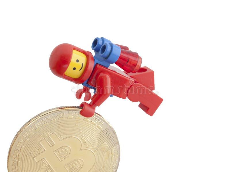 Venedig Italien - Januari 07, 2018: En astronaut som det Lego diagramet anseende bredvid Bitcoin mynt, Januari 07, 2018 i Venedig royaltyfri fotografi