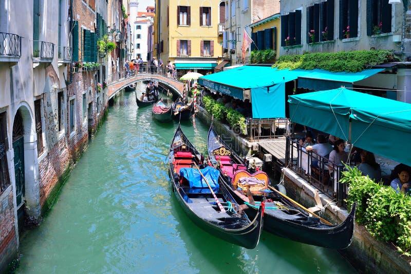 VENEDIG ITALIEN - MAJ, 2017: Härlig perspektivisk förkortning av byggnader på en liten kanal i Venedig, med detaljen av gondol tv royaltyfri foto