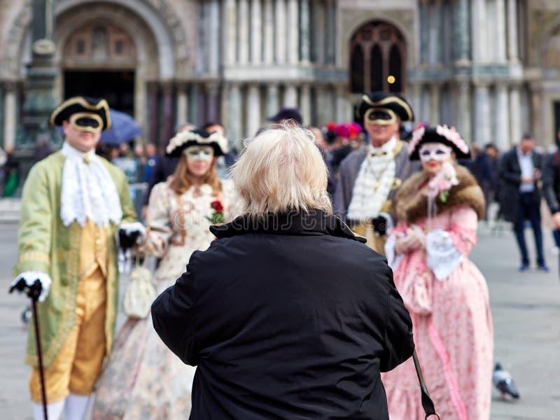 Venedig Italien - mars 1, 2019 a-turist att förbereda sig för att ta ett foto av en grupp av personer som förställas i karneval a royaltyfri foto