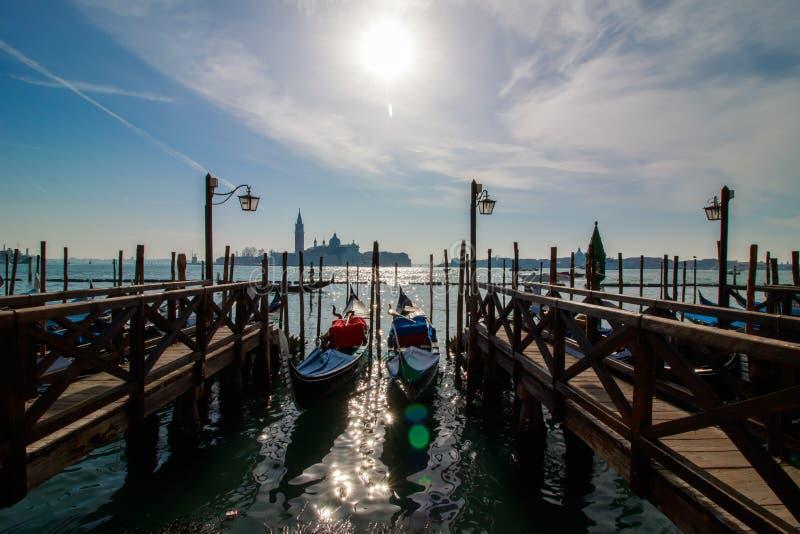 Venedig italiensk stadssikt med gondoler som parkeras på kusten, kanaler och det bro-, havs- och molnhimmellandskapet på den soli fotografering för bildbyråer