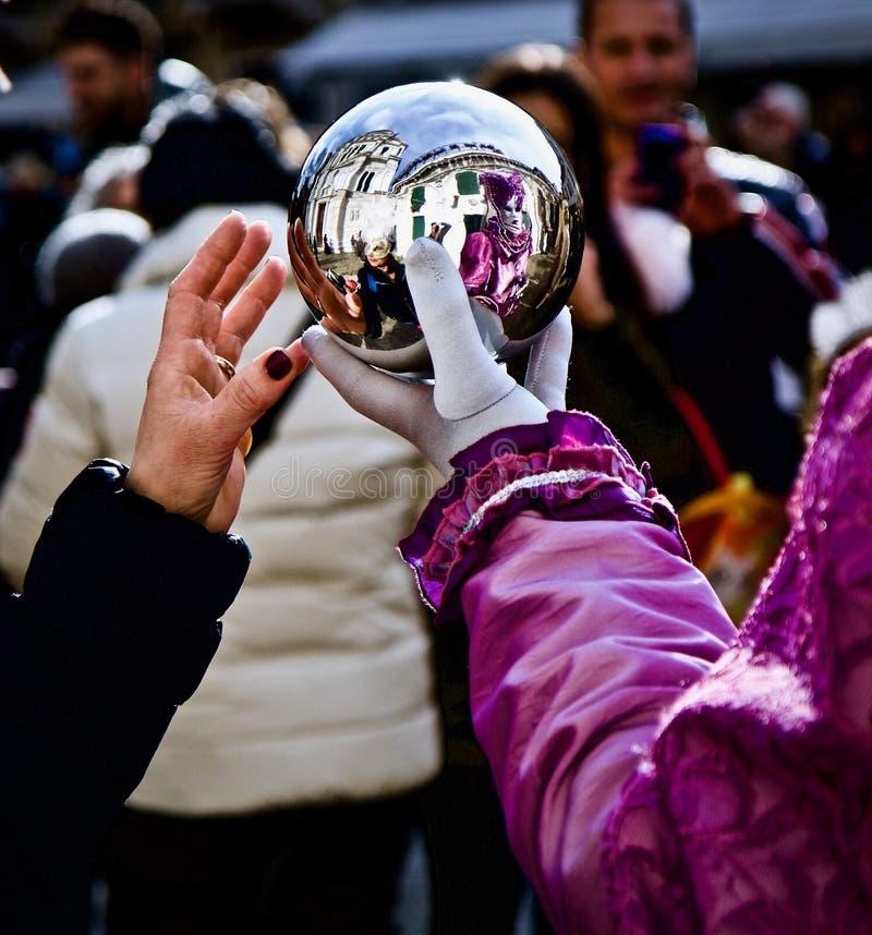 Venedig-Karnevals-Teilnehmer und Feiernder, die silbernen Ball untersuchen stockfoto