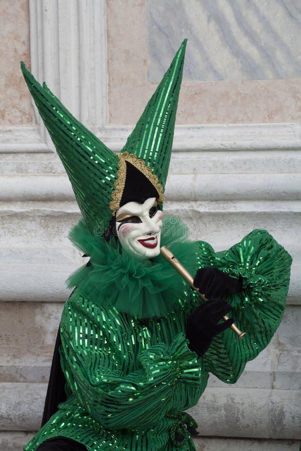 Venedig-Karnevals-Zahl in einem bunten grünen und schwarzen Kostüm und Maske, die eine Flöte Venedig Italien Europa spielt lizenzfreie stockbilder