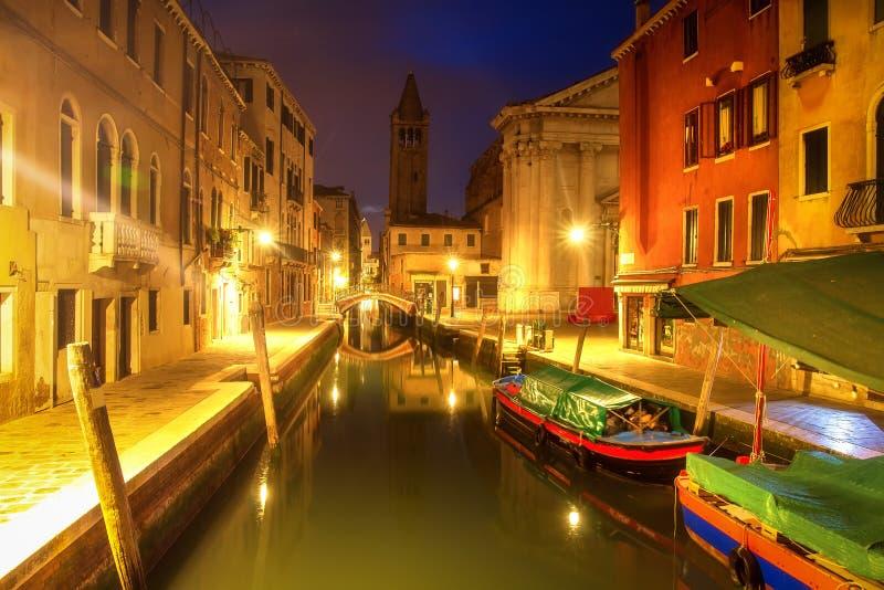 Venedig nachts, Italien Schöne Ansicht über schmalen venetianischen Kanal mit Booten nachts Venezia belichtete durch citylights lizenzfreie stockfotografie