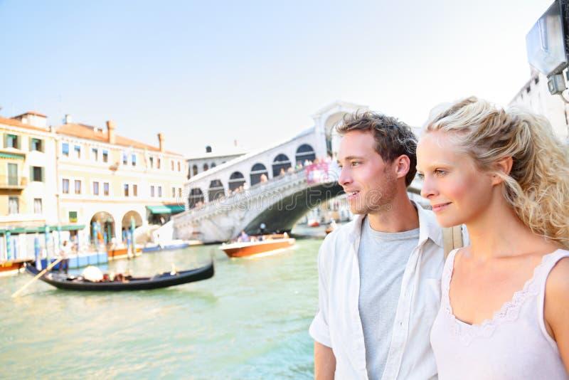 Venedig-Paare durch Rialto-Brücke auf Grand Canal stockbilder