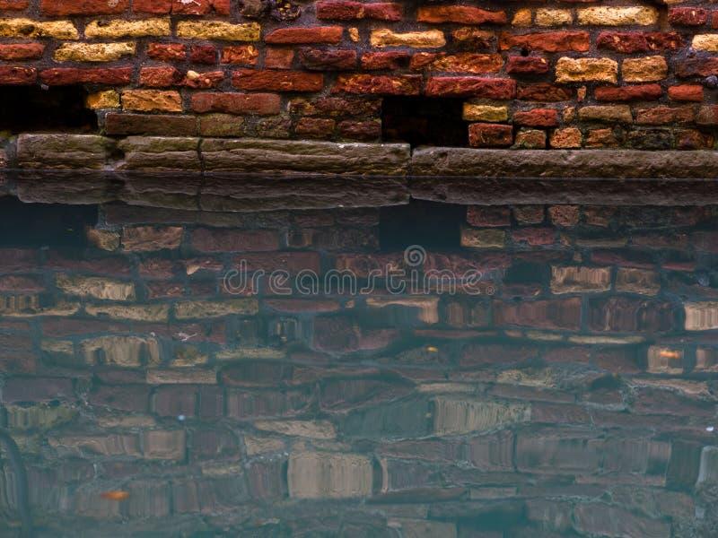 Venetië gaat onder het water, textuur van de bakstenen muur en water in het kanaal royalty-vrije stock afbeeldingen