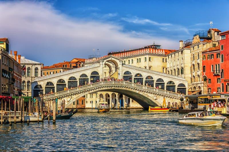 Venetië, Italië - Augustus 22, 2018: De Rialto-brug, een vaporetto, een veerbootligplaats en gondels in Grand Canal royalty-vrije stock fotografie