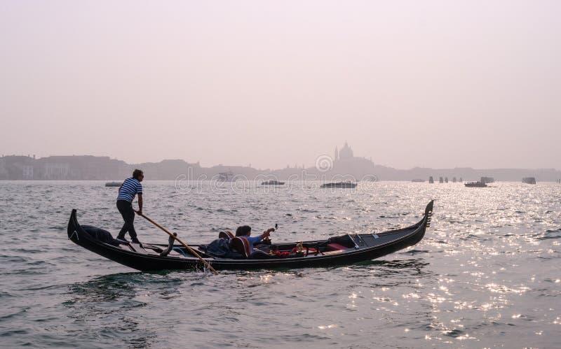 Venetië, Italië - Oktober 13, 2017: De gondelier stelt een gondel met toeristen in de wateren van het Grande-Kanaal in werking royalty-vrije stock foto's