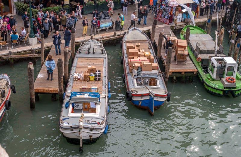 Venetië, Italië - Oktober 13, 2017: pijler op Grand Canal Voor het eerste plan, het leegmaken van vrachtboten op stock afbeelding