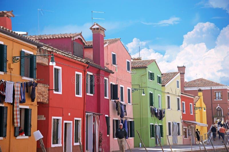 VENETIË, ITALIË, OP 13 APRIL, 2015 Buranoeiland, multi-colored huizen van plaatselijke bewoners Koffie op de bank van het kanaal  stock foto's