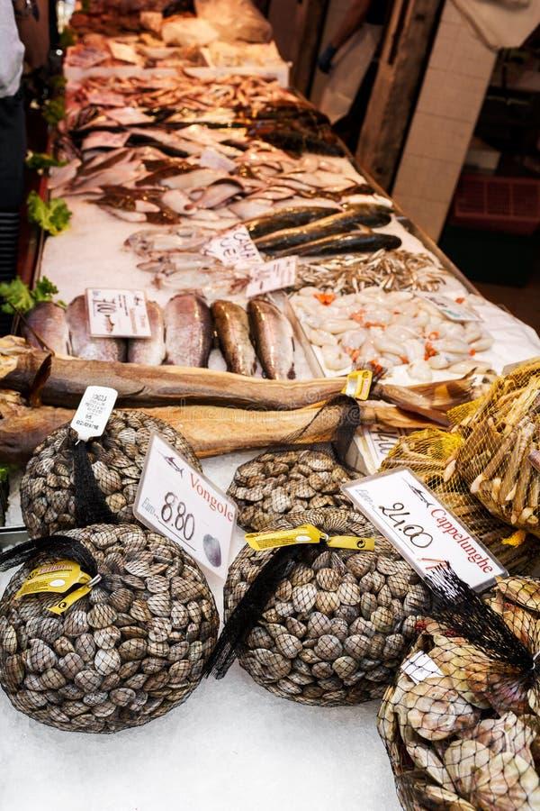 Venetië, Italië - September, 2016: De Markt van Rialtovissen De verse zeevruchten worden getoond op verpletterd ijs onder neonlic royalty-vrije stock afbeelding