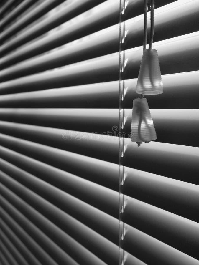 Venetian blind: cord detail angle - v. Black and white venetian blind composition with cord detail - vertical stock photo