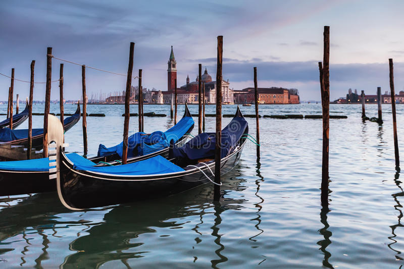 Venetian gondolas at sunset. The popular gondola pier in Venice stock photos