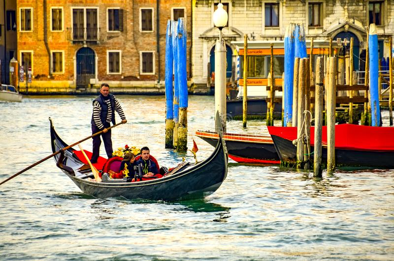 Venetian gondolier punting gondola through Grand Canal waters of Venice Italy stock image