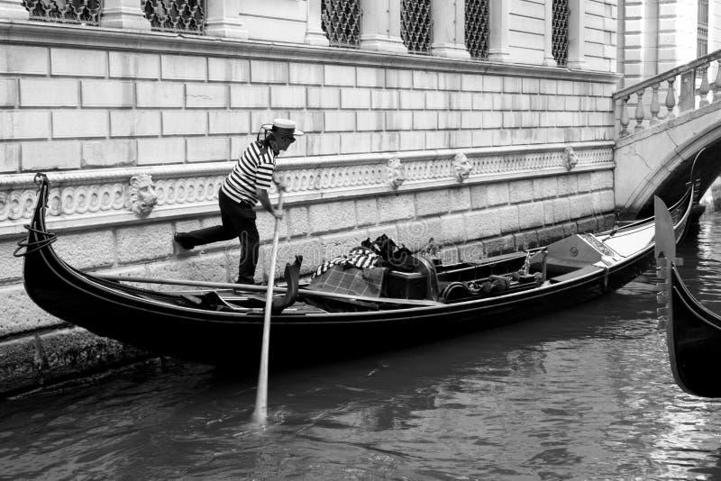 Venetian gondoljär i en kanal royaltyfri foto