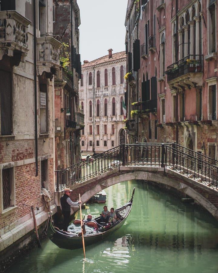 Venetian gondolritt till och med en kanal arkivbild