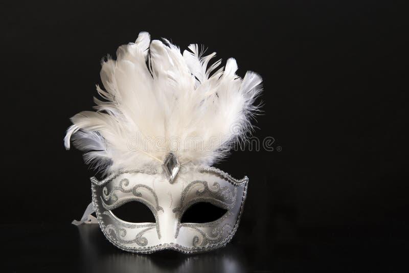Venetian karnevalmaskering för vit och för silver med fjädrar på en svart bakgrund arkivbild