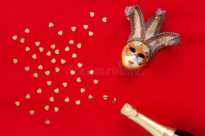 Venetian mask and champagne bottle with heart shape gold glitter confetti. Top view, Close up on red background stock photos