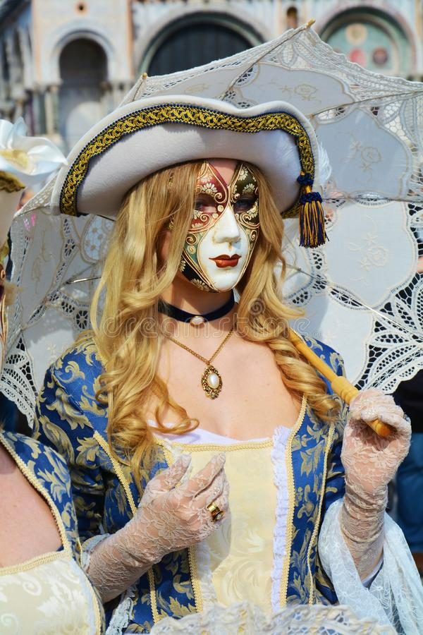 Venetian mask, Venice, Italy, Europe. Elegant blue Venetian mask with golden decorations, holding an umbrella, in St Mark`s Square, during the Carnival of Venice royalty free stock image