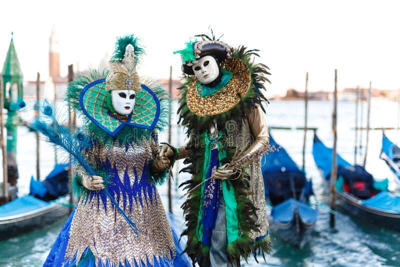 Venetian maskerad modell från den Venedig karnevalet 2019 med gondoler i bakgrunden arkivfoto