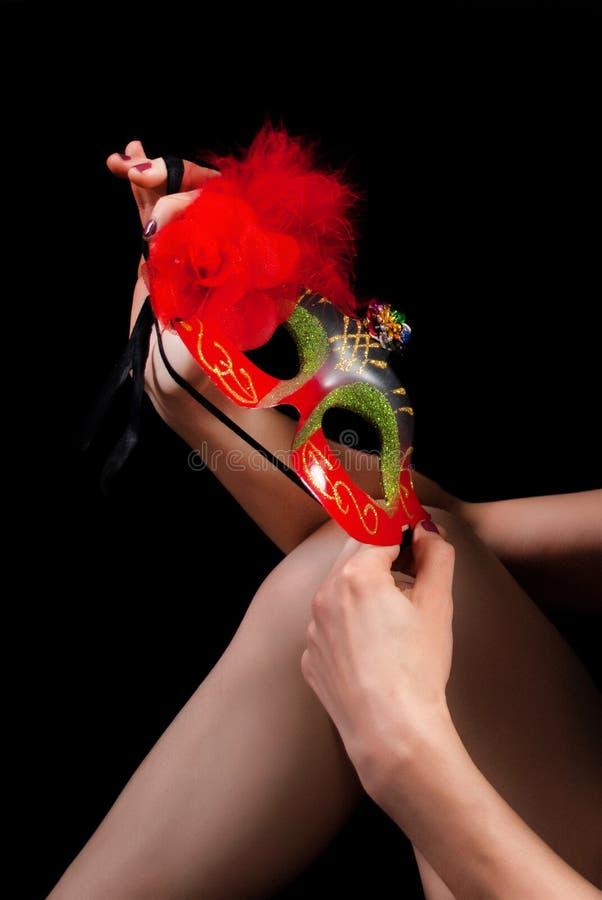 Venetian maskering för röd framsida i kvinnliga händer på benknäet som isoleras på svart arkivbild