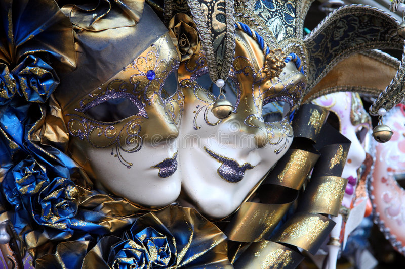 Venetian masks. Row of venetian masks in gold and blue royalty free stock images