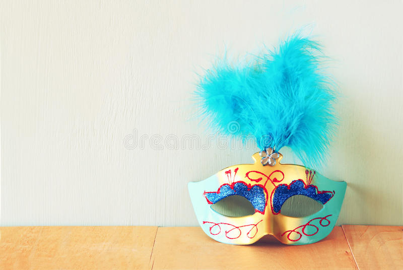 Venetian masquerade mask on wooden table. retro filtered image stock photos