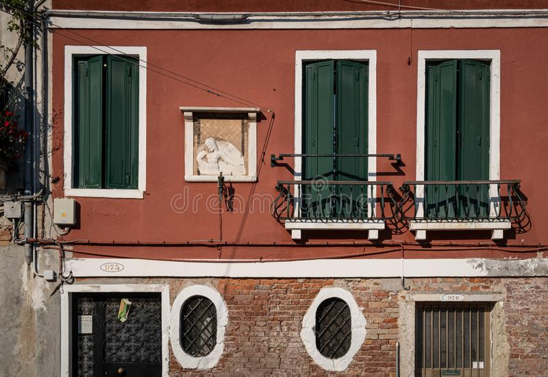 Venetian red facade of old house with religious scene, green windows and typical oval windows. Venice, Italy royalty free stock photo