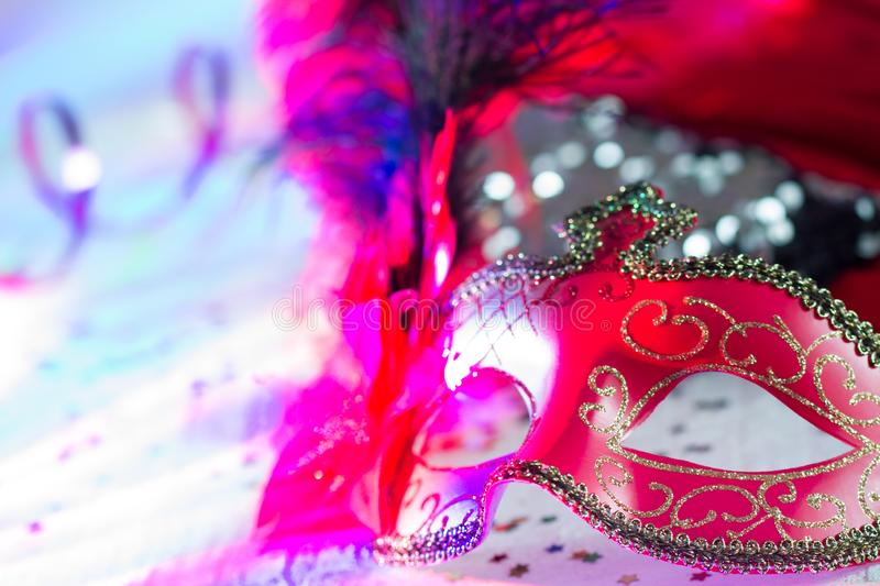 Venetian red mask on defocused carnival party background. Closeup royalty free stock image