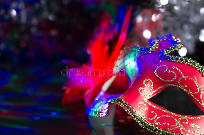 Venetian red mask on defocused carnival party background. Closeup stock images