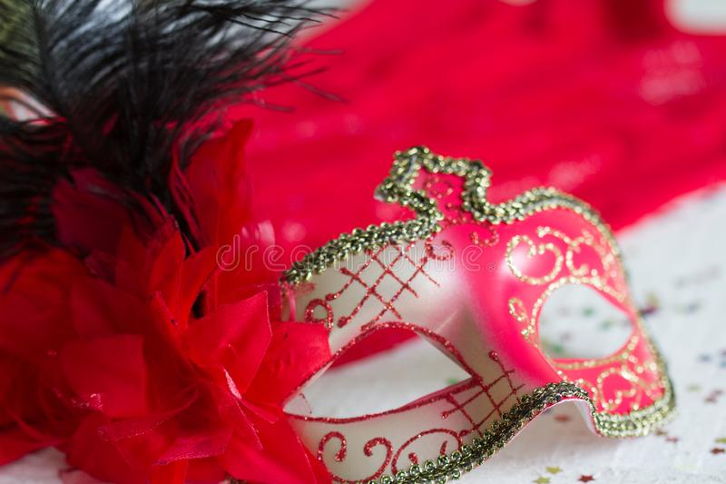 Venetian red mask on defocused carnival party background. Closeup stock photos