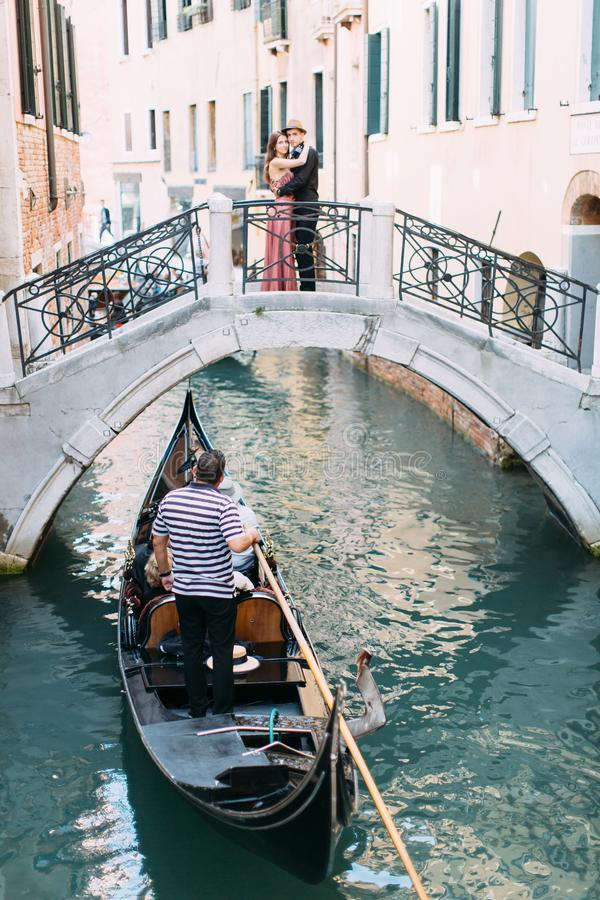 Venetian scenery with a gondola on a narrow canal. Romantic couple standing on the bridge of venetian canal. stock photo