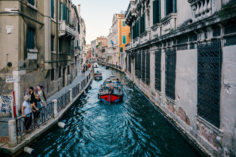 Venetian street canal with various boats on it, tourists walk alongside. royalty free stock photography