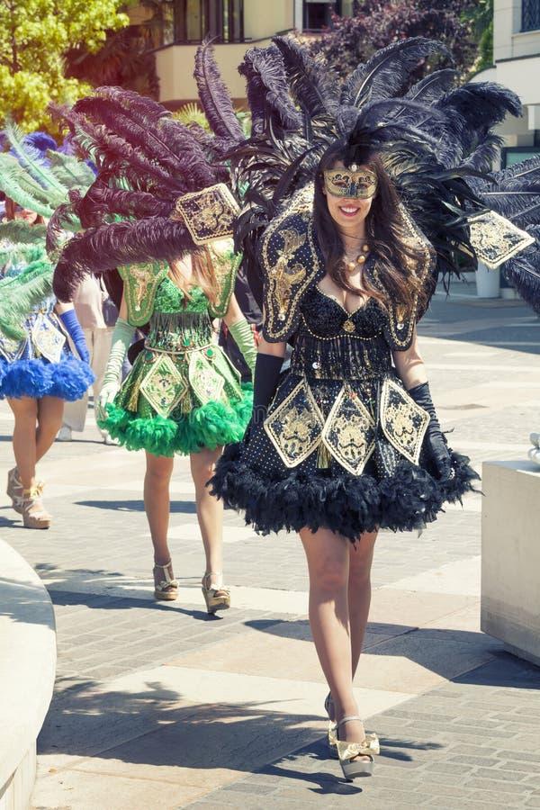 Venetianische schwarze Kostüme, schönes Mädchen, das in die Straße vorführt stockfotografie