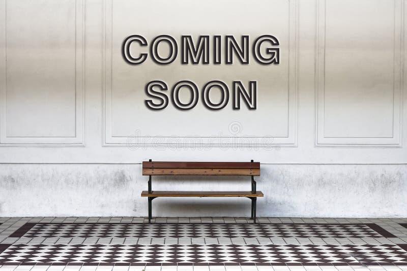Venez bientôt écrit sur un mur au-dessus d'un banc en bois - ima de concept image libre de droits